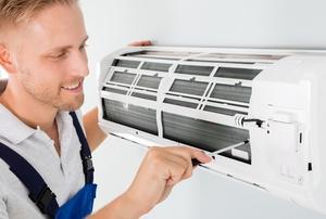 A man works on an AC unit.