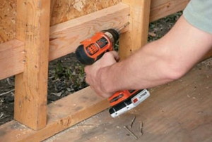 a man drilling new wood onto the bottom of a shed