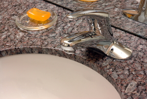 a corian countertop with a sink and a a glass cup with orange soap  inside