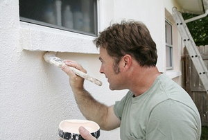Painter at work applying white to the exterior of a home.
