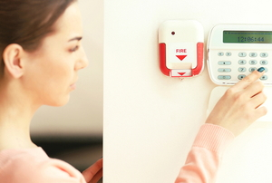 woman setting a security home alarm system