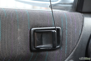A coat hanger being used to open a locked car door handle.