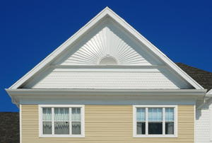 A vent on the white gable of a private home.