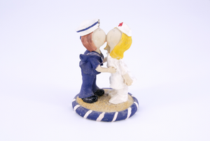 man and woman kissing figurine