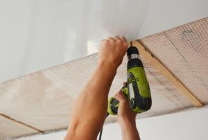 hands drilling plastic ceiling panels