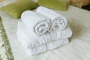 A stack of white bath towels on a bed with green pillows.