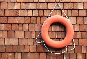 A red life ring hanging against wood siding.