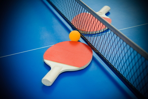 Two ping pong paddles and a ping pong ball on a table.