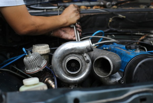 A man works on a turbo diesel engine.