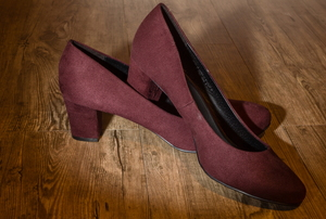 A pair of wine-colored, suede high heels.