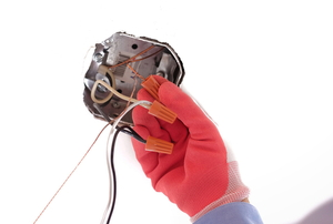 gloved hand working with wires in ceiling light fixture