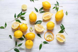 An assortment of lemons on a wood surface.