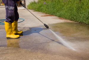 a person pressure-washing concrete
