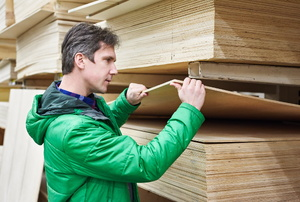 a person in green looking through plywood