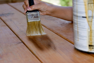 Using a brush to apply stain to outdoor wooden furniture.