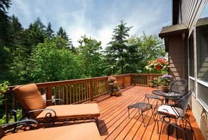 A stained deck in a sunny backyard.