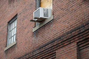 air conditioner mounted in window on brick facade