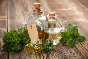Two bottles of olive oil sit on a wooden surface with herbs surrounding them.