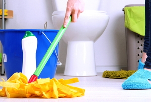 a woman cleaning a bathroom floor with a mop.