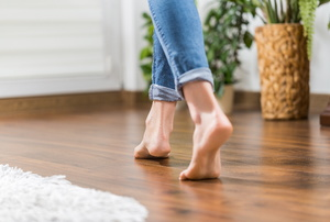 A wood laminate floor with someone walking on it.