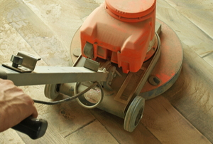 hands using large floor sander on wood floor