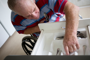 A kitchen drawer with cutlery and a man in a wheel chair reaching in.
