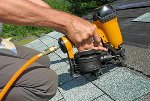Man using a pneumatic nail gun to attach roofing materials