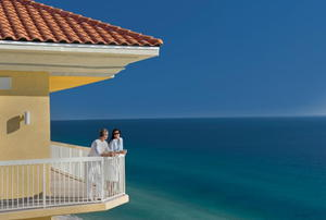 A couple on the balcony of a beach house, overlooking the ocean.