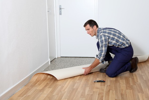 A man installs linoleum floors.