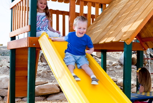 A kid going down a slide on playground equipment
