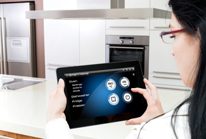 A woman accessing her tablet in her smart kitchen.