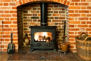 fire burning in wood stove surrounding by brick