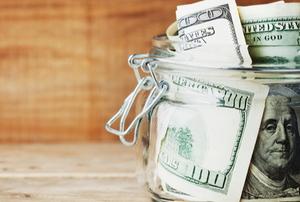 a savings jar with hundred dollar bills