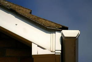 A close-up of the corner of a roof, with soffit, shingles, and gutter visible.