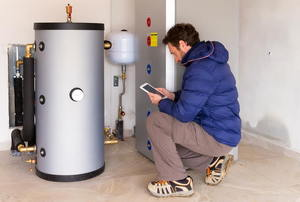 Man kneeling next to a water heater