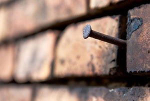 A nail in a brick wall.