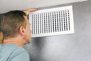 A man checking an air vent on a wall.