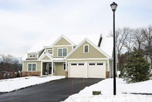 A house surrounded by snow with a clear asphalt driveway.