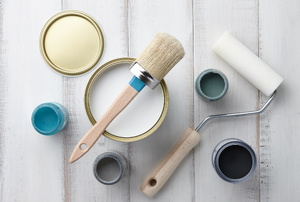 A collection of paint cans and paint tools.