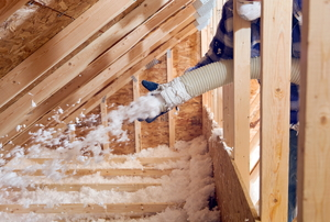 Side view of a man spraying cellulose insulation into a triangular space on one side of an attic.