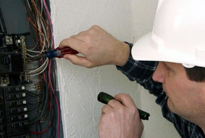 A man examines a circuit breaker.