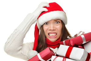 A woman wearing a Santa house and holding Christmas presents with a stressed look on her face.