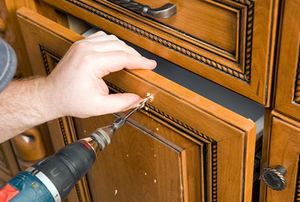 Cabinet Worker Drilling Hole for a new Drawer Pull Handle