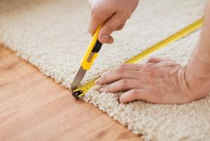 A man measures carpet.