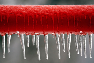 A length of red piping with icicles hanging off of it.