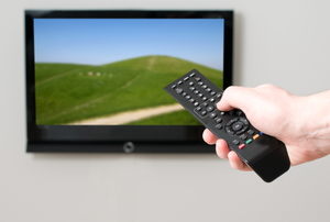 Pointing a remote at a wall-mounted flat screen TV