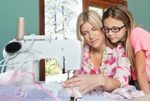 girl watching a woman sew