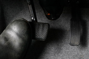 A foot stepping on a brake pedal inside a vehicle.