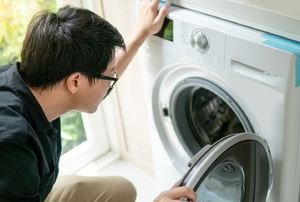 Person looking inside an open dryer
