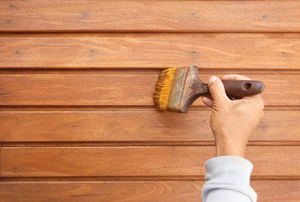 A woman stains a deck.